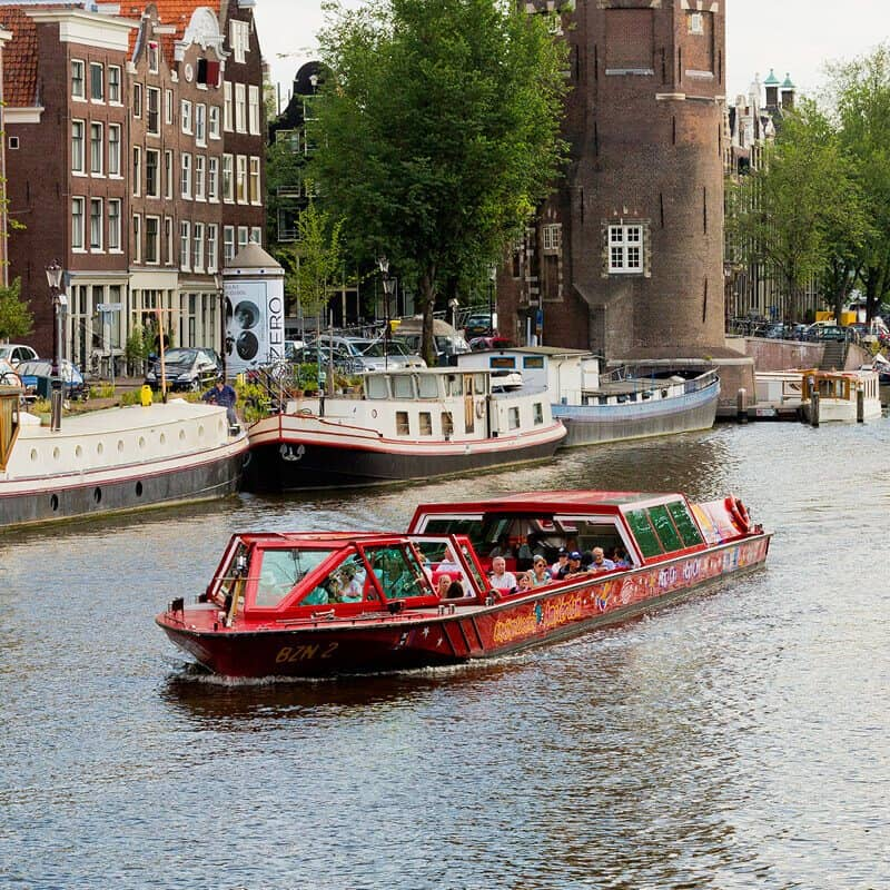 City Sightseeing Hop-on Hop-off by boat in Amsterdam on the water with houses and tower on the background